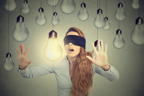 Blindfolded woman walking through lightbulbs searching bright idea